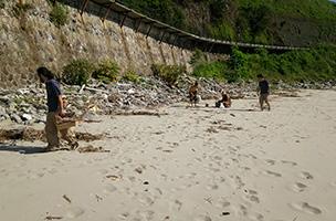 「土の民」の活動の一つ、ビーチクリーニング。海岸でのゴミ拾いで得た流木や割れたビンなどは「森の民」の物作りの材料に